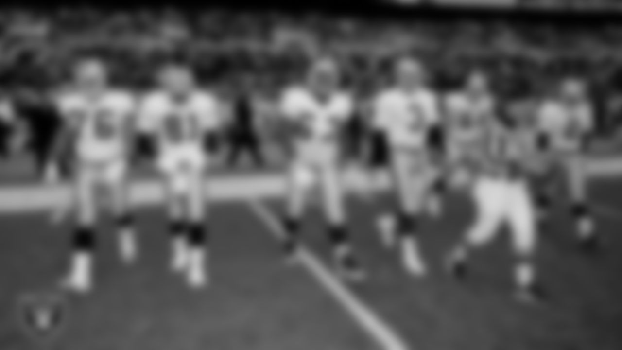 Oakland Raiders guard Steve Wisniewski (76), wide receiver Tim Brown (81), defensive tackle Russell Maryland (67), quarterback Jeff George (3), linebacker Greg Biekert (54) and punter Leo Araguz (2) walk out to the center of the field for the coin toss before the regular season away game against the the Baltimore Ravens at Ravens Stadium at Camden Yards, Sunday, November 8, 1998, in Baltimore, Md.