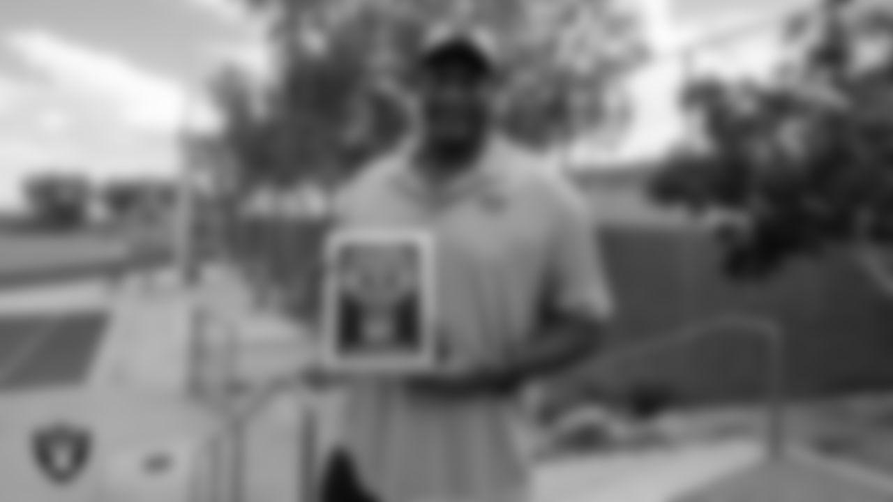 Las Vegas Raiders alumnus Napoleon McCallum holds the Tom Flores Coach of the Week award for Desert Oasis High School football coach Brant Smith.