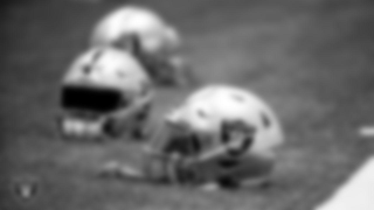 Las Vegas Raiders helmets on the field for a walkthrough.