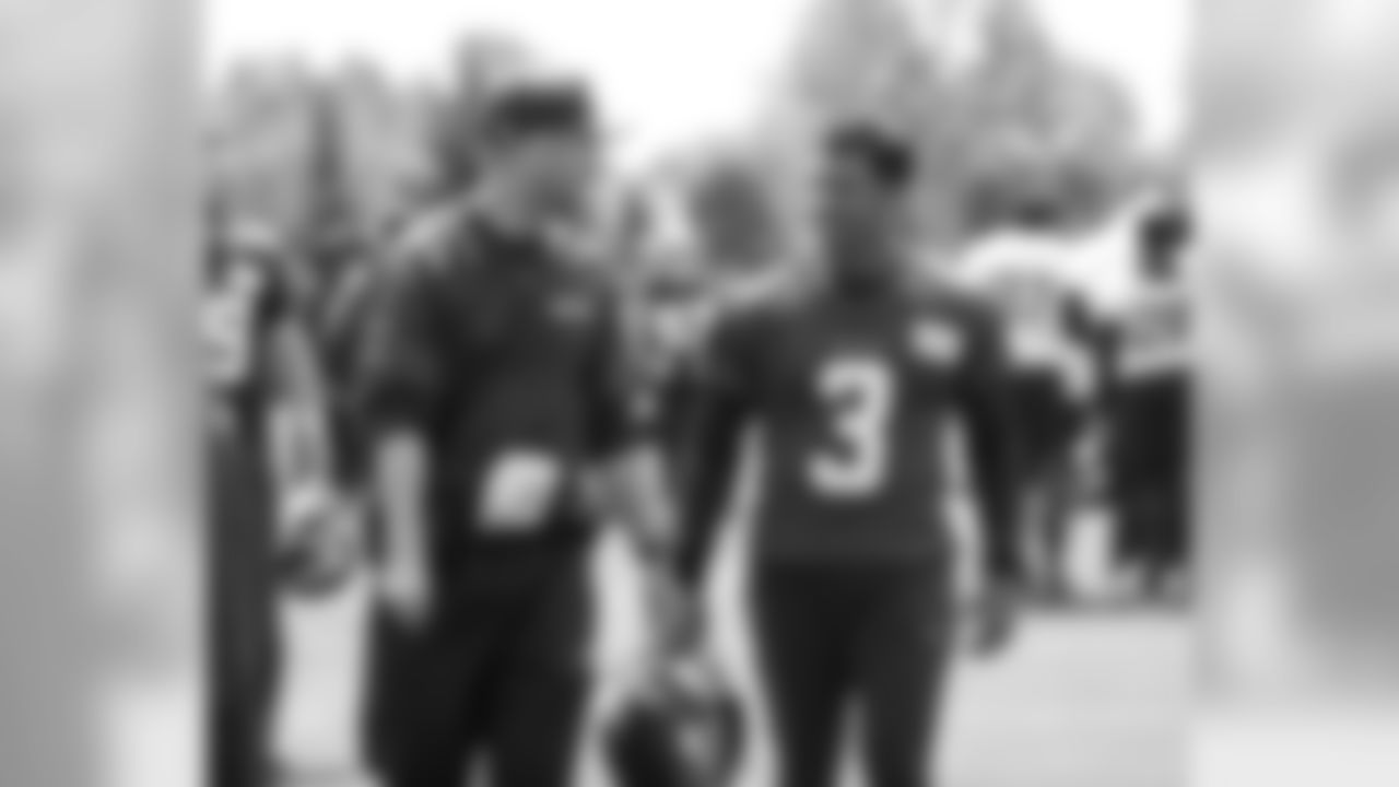 Offensive coordinator Brian Schottenheimer, left, and quarterback Russell Wilson.
