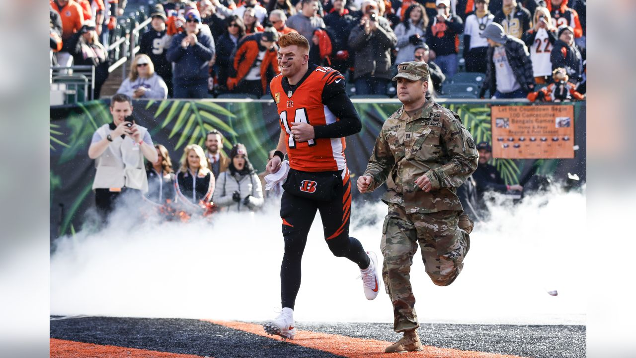 Cincinnati Bengals quarterback Andy Dalton (14) runs onto the field with a member of the armed forces before an NFL football game against the New Orleans Saints, Sunday, Nov. 11, 2018, in Cincinnati. (AP Photo/Frank Victores)