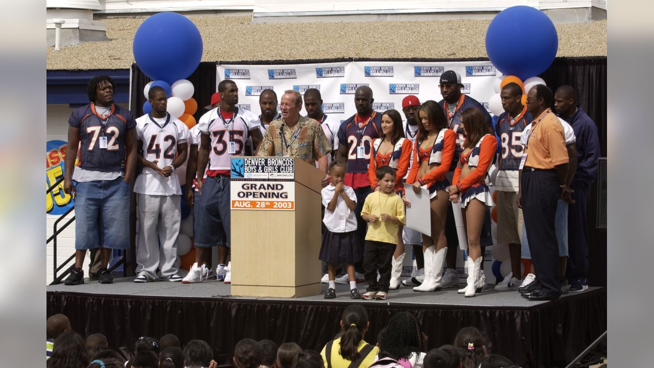 Pat Bowlen speaks at the ceremony commemorating the grand opening of the Denver Broncos Boys & Girls Club in 2003. Several players were on hand, including Rod Smith, Ian Gold, and Deltha O' Neal, along with Pat Bowlen, Miles, and the Denver Broncos Cheerleaders to help with the celebration.