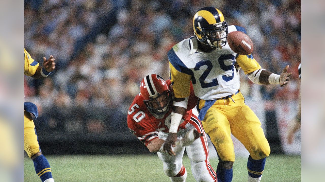 Rams Eric Dickerson looks to the football as he is hit from behind by Falcons Buddy Curry during the first quarter on Monday, Oct. 22, 1984 in Atlanta.  AP Photo / Joe Sebo