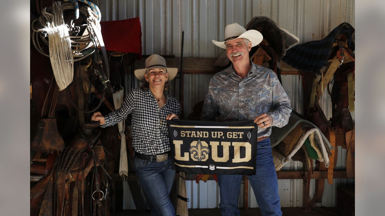 Cynda and Keith Unger, parents of New Orleans Saints center Max Unger, hold a Saint's flag inside a tack room on McCandless Ranch, Wed, Jan. 16, 2019, in Hookena, Hawaii. NFL football center Max Unger grew up on his family's McCandless Ranch, a 7000 acre working cattle ranch that starts on the slopes of Mauna Loa stretches down to Hookena Beach. According to family, Max spent time riding horses and working on the ranch. (Marco Garcia for the New Orleans Saints)