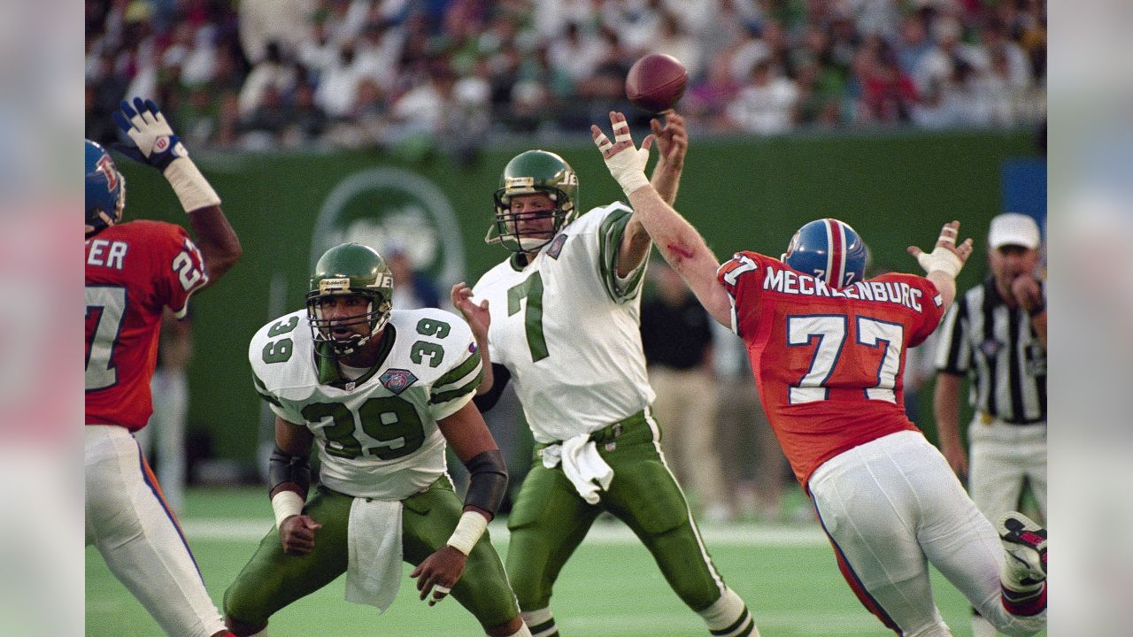 New York Jets running back Johnny Johnson (39) blocks for quarterback Boomer Esiason (7) as Denver Broncos linebacker Karl Mecklenberg (17) reaches for the ball in second half action of their NFL football game at Giants Stadium in East Rutherford, N.J., Sept. 11, 1994. The Jets won 25-22. (AP Photo/Bill Kostroun)