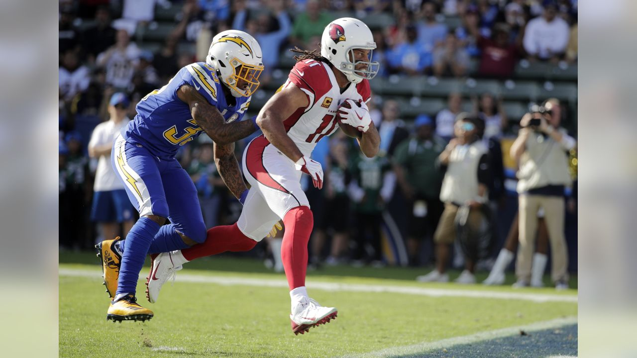 Arizona Cardinals wide receiver Larry Fitzgerald, right, runs past Los Angeles Chargers free safety Derwin James on a touchdown reception during the first half of an NFL football game Sunday, Nov. 25, 2018, in Carson, Calif.