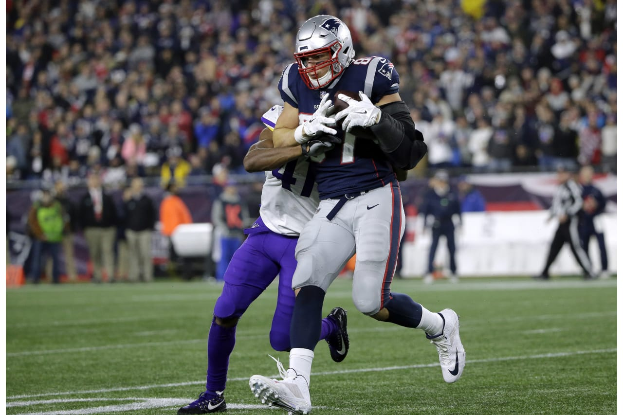 New England Patriots tight end Rob Gronkowski runs after catching a pass as Minnesota Vikings defensive back Anthony Harris, rear, tries to tackle him during the first half of an NFL football game, Sunday, Dec. 2, 2018, in Foxborough, Mass. (AP Photo/Steven Senne)