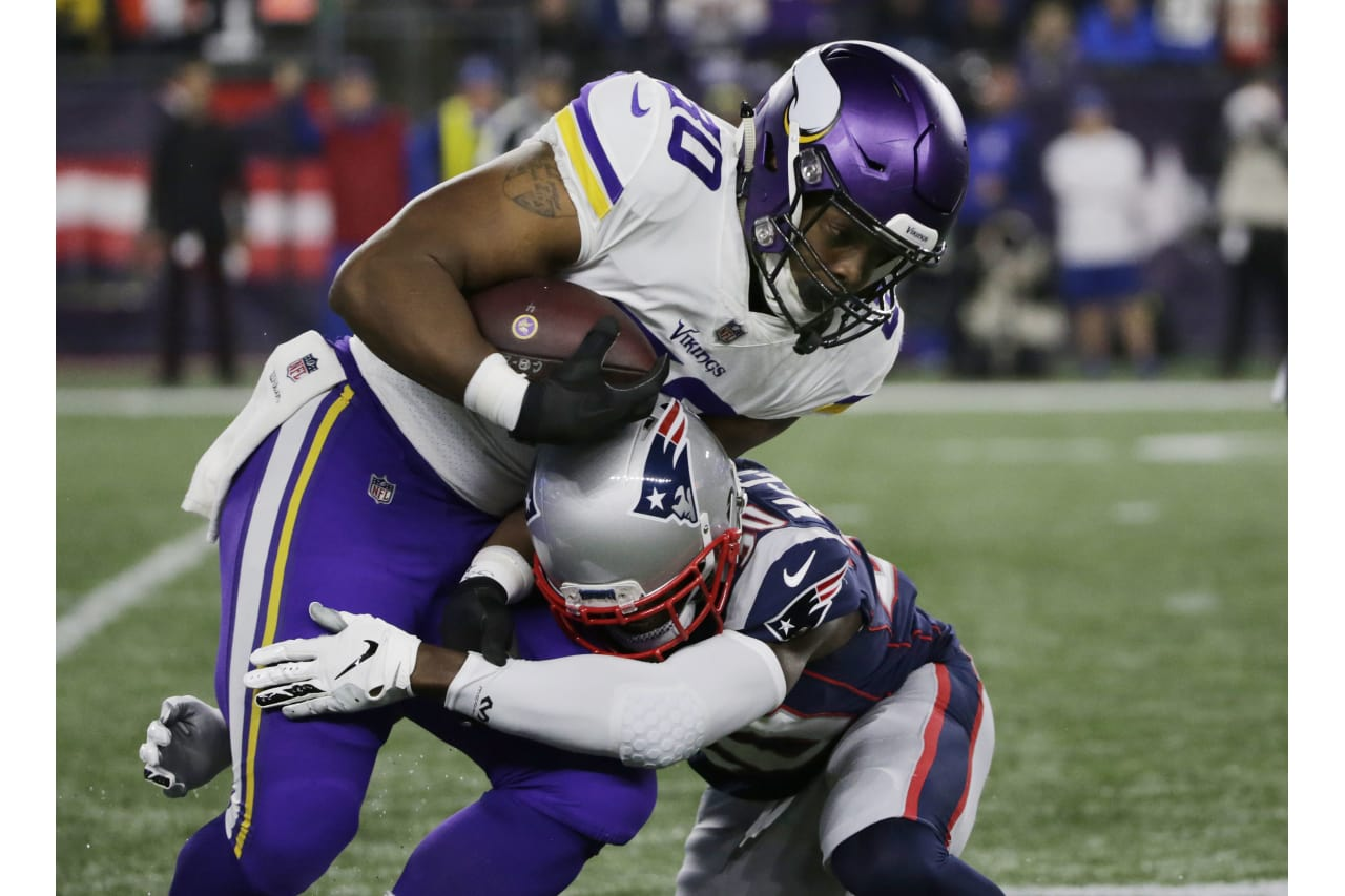 New England Patriots defensive back Jason McCourty, right, tackles Minnesota Vikings fullback C.J. Ham during the first half of an NFL football game, Sunday, Dec. 2, 2018, in Foxborough, Mass. (AP Photo/Elise Amendola)