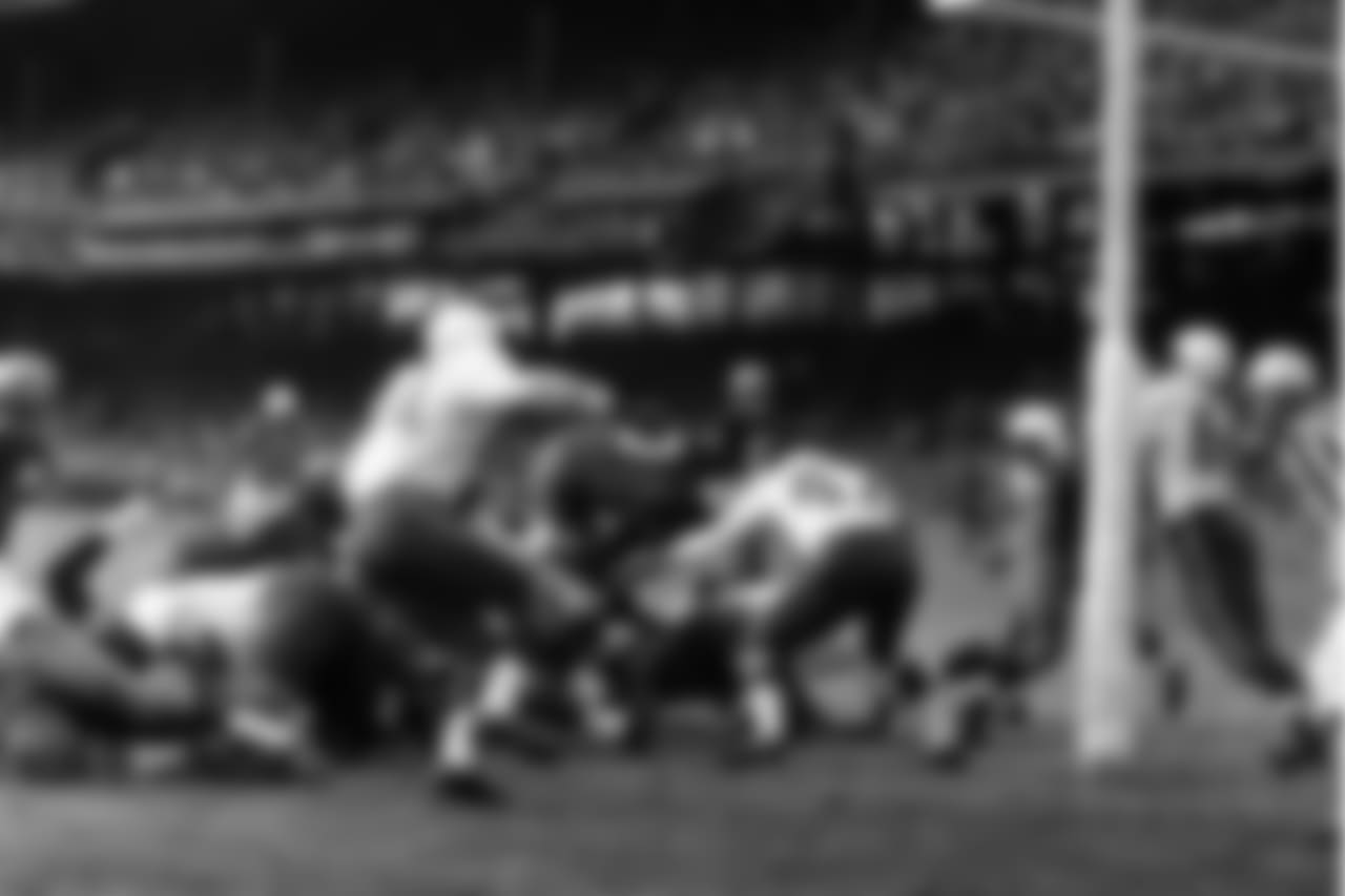 Johnny Olszewski, Washington Redskins fullback, vaults across the line for a first-quarter touchdown against the Chicago Cardinals, Nov. 9, 1958, Washington, D.C. He is headed right for Bobby Gordon (47), Cardinal back. Dick Lane of the Cards is at left. Olszewski scored from one yard out.