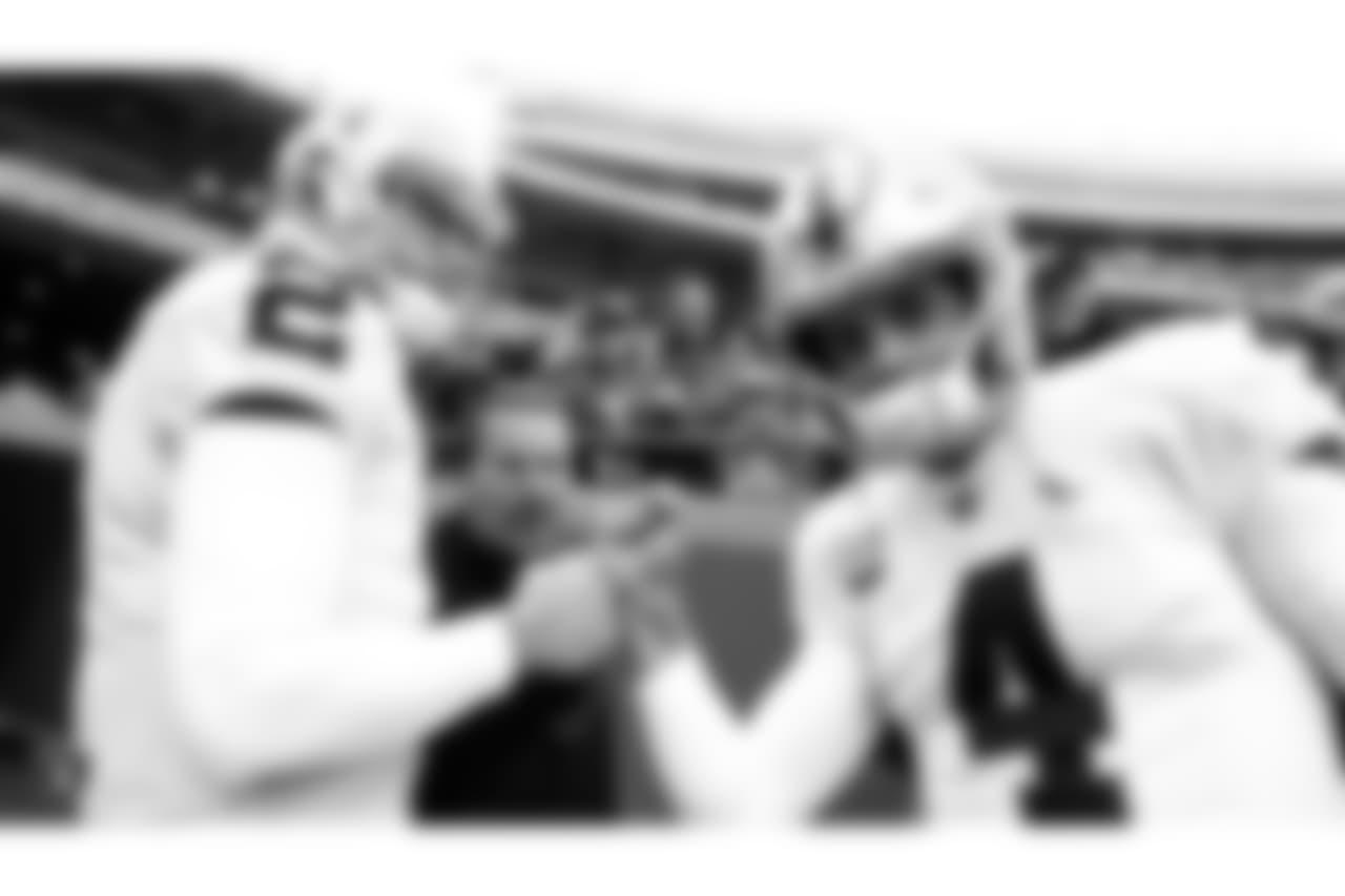 Oakland Raiders quarterback AJ McCarron (2), offensive coordinator Greg Olson, and quarterback Derek Carr (4) huddle up before their regular season game against the Kansas City Chiefs at Arrowhead Stadium, Sunday, December 30, 2018, in Kansas City, Missouri. The Oakland Raiders lost 35-3.