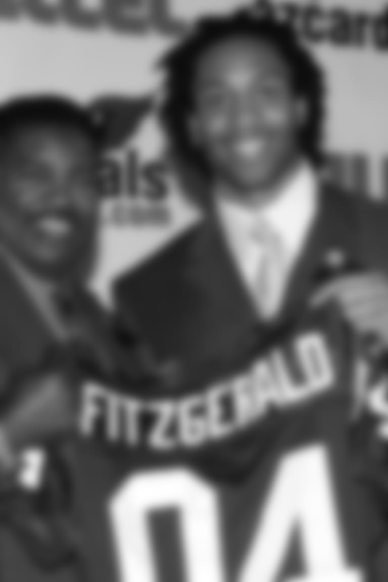 First-round pick Larry Fitzgerald holds up his jersey with coach Dennis Green during Fitz's introductory press conference in 2004